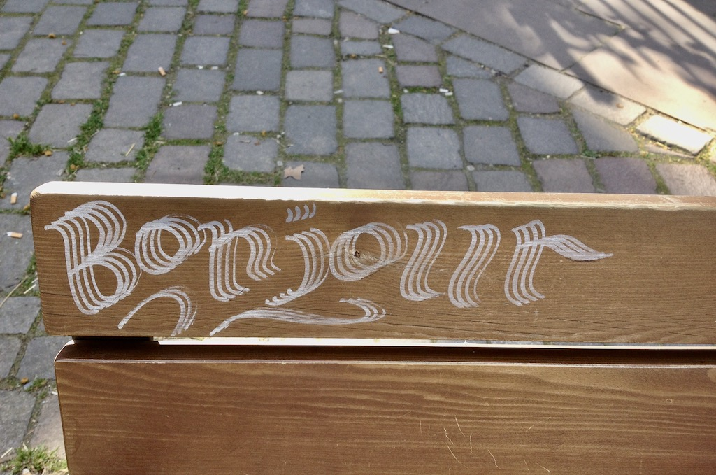 Bonjour-Graffiti auf einer Parkbank